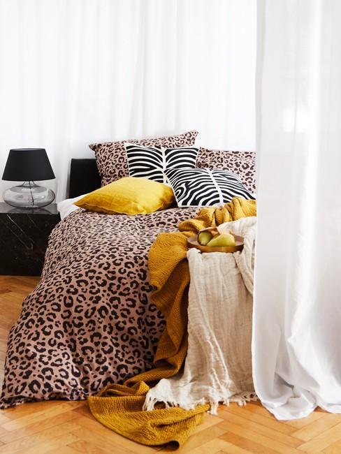 Sypialnia z łóżkiem z pościelą w tropikalne wzory oraz czarny stolik nocny