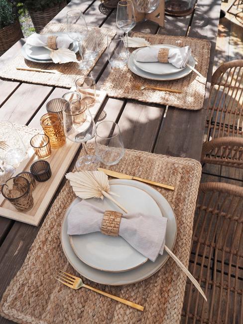 Letnia aranżacja stołu z kamionkową zastawa, złotymi sztućcami oraz świecznikami z przydymionego szkła
