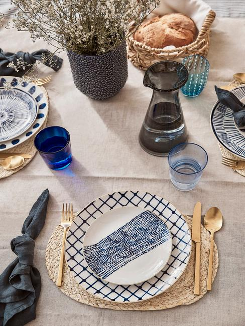 Fragment stołu udekorowanego w barwach czarno-niebieskich z kamionkową zastawą, złotymi sztućcami oraz wazonem świeżych kwiatów