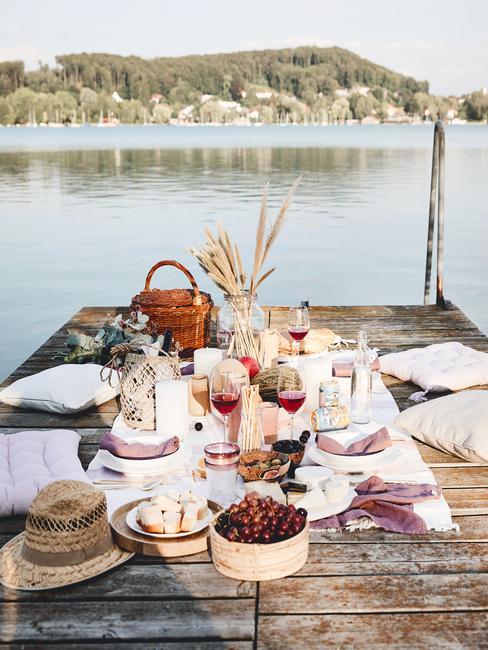 Piknik zorganizowany nad jaziorem z akcesoriami: kocem, poduszkami, wazonem suszonej trawy oraz przekąski