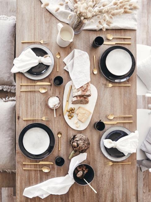 Drewniany stół z biało-czarna zastawą i złotymi sztućcami