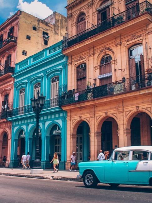 Niebieski samochód przed kolorowymi domami na Kubie.