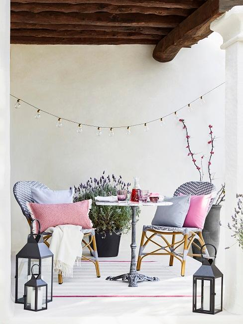 Balkon mit einem Tisch, zwei Stühlen und reichlich Deko: Lichterkette, Kissen, Pflanzen und Laternen