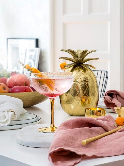 Kieliszek koktajlowy na złotej nóżce obok złotego ananasa dekoracyjnego na stole w jadalni.