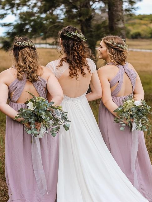 Braut und Ihre zwei Trauzeuginnenvon hinten Outdoor