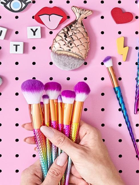 pinceles para maquillaje en un fondo rosa