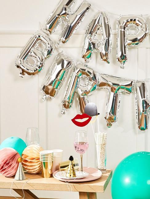 Decorazione della tavola del compleanno con ghirlanda Happy Birthday in argento, pompon di carta, cappelli da festa e divertenti stuzzichini.