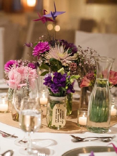 Różowe i filetowe kwiaty na stole weselnym