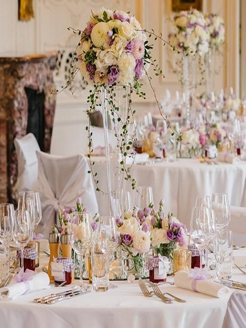 Gedeckte runde Hochzeitstische dekoriert mit Blumen