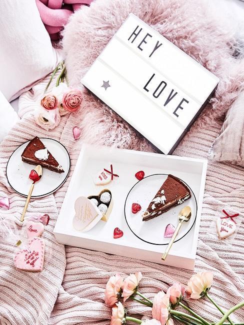 Tablett mit Kuchen auf rosa dekoriertem Bett