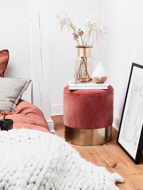 Modernes Schlafzimmer mit einem Pouf als Abstelltisch, darauf Bücher und Deko