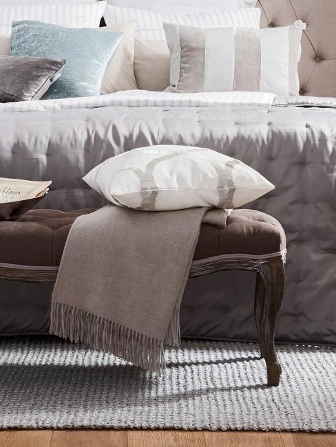 Ein Bett im Landhausstil in gedeckten Farben, davor eine Bettbank