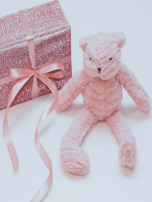 Rosa Teddy neben einem rosa verpackten Geschenk mit Glitzer