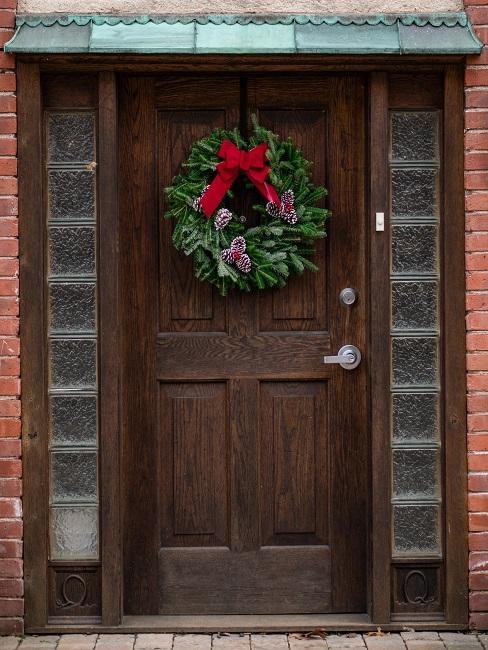 Haus von außen mit dunkler Holztüre, daran ein Weihnachtskranz als Deko für draußen