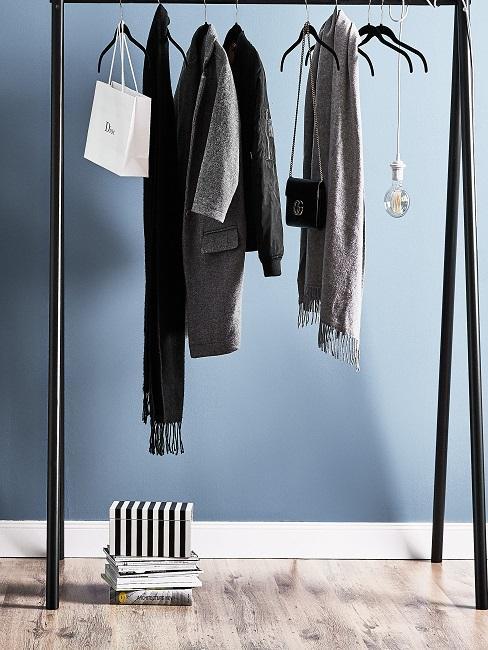 Schwarze Kleiderstange vor blauer Wand