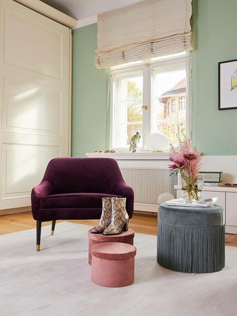 Schlafzimmerecke von Tamara Gräfin von Nayhauß mit einem Sessel in Violett vor Aufbewahrungsboxen in Rosa und einem Pouf in Blaugrau, im Hintergrund eine Wand in hellem Grün