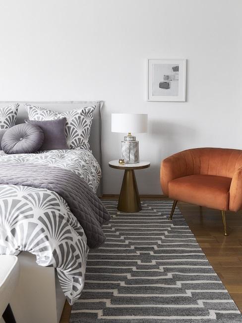 Ein Bett mit grau gemusterter Bettwäsche und grauen Kissen, passend dazu der grafisch gemusterte Teppich, daneben ein Samt Sessel in Braun