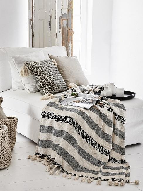 Boho Schlafzimmer mit grauen Kissen und grau-weißer Decke