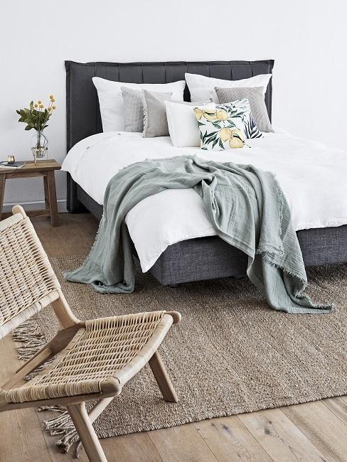 Boho Schlafzimmer Materialmix schwarzes Bett mit grüner Decke und Juteteppich