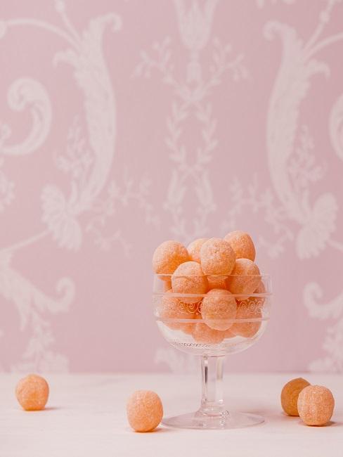 Ein Glas mit Bonbons in Orange auf einem Tisch vor einer rosafarbenen Wand mit Muster