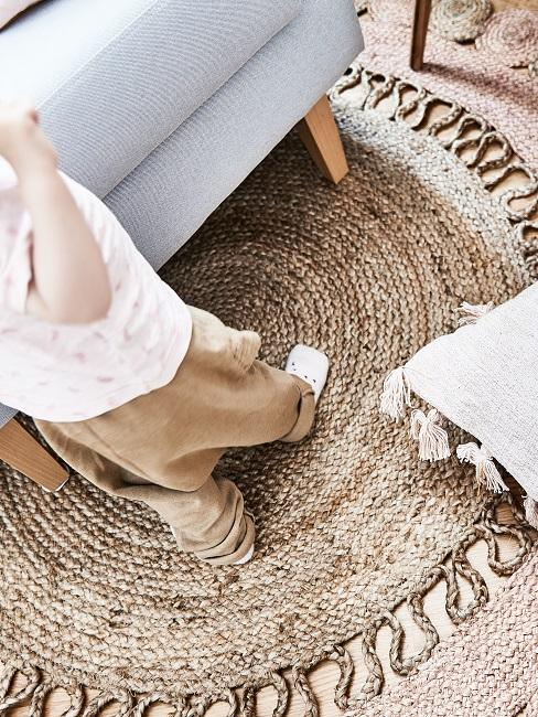 Ein runder Jute Teppich neben einem Sofa in Hellgrau