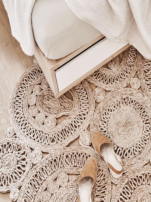 Runder Jute Boho Teppich mit Schuhen vor einem hellen Holzbett