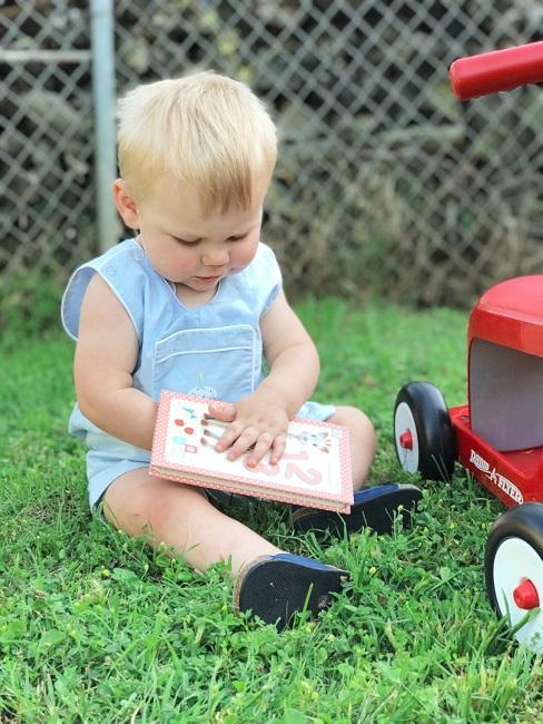 Geschenke zum 1. Geburtstag Baby mit Buch auf Wiese