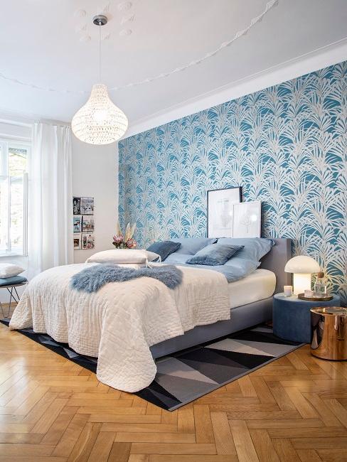 Bett in Grau, hinter dem Bettkopf eine blau gemusterte, tapezierte Wand