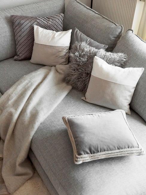 Graue Couch mit Kissen und einer Decke für die maximale Gemütlichkeit bei Motsi Mabuse im Wohnzimmer