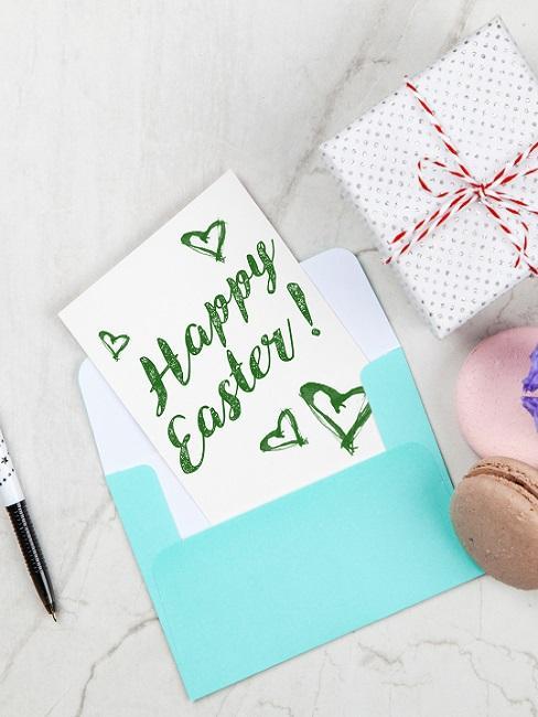 Osterkarte mit Umschlag neben einem verpackten Geschenk