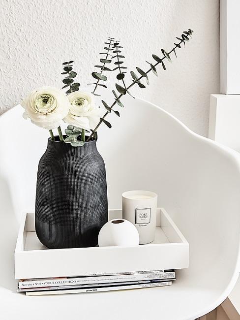 Japandi Deko: Schwarze Vase mit Blumen neben Kerze auf weißem Tablett auf weißem Stuhl