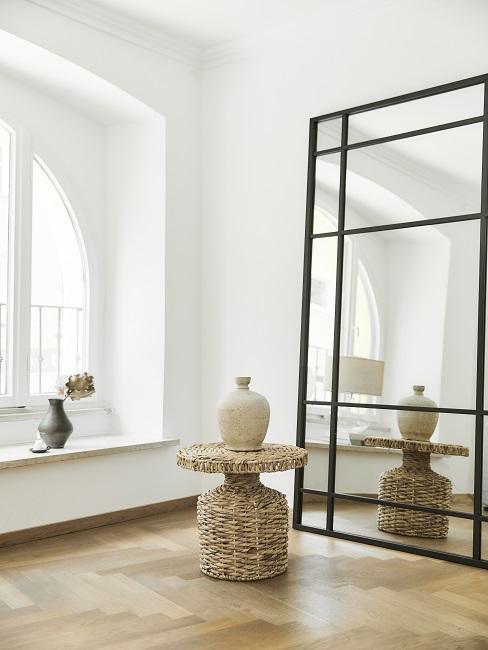 Japandi Deko: Schwarze Vase auf Fensterbrett und cremefarbene Vase auf Beistelltisch aus Rattan neben Wandspiegel