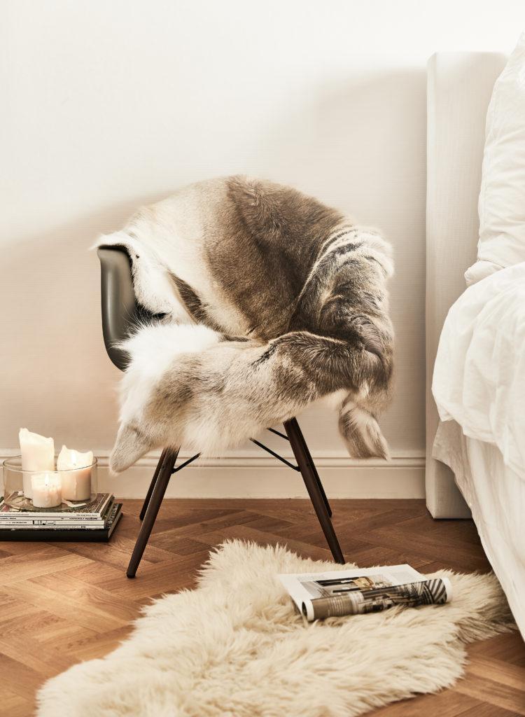 Luxus Schlafzimer mit einem Stuhl mit gemütlichem Fell neben dem Bett sowie romantischer Kerzendeko