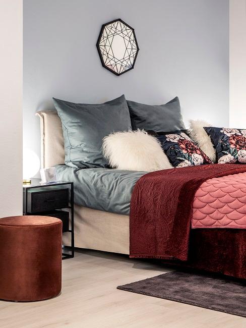 Schlafzimmer mit einer hellblauen Wand hinter dem Bettkopf, vielen kuscheligen Betttextilien wie Decken und Kissen sowie einem Pouf, alles in Blau- und Rottönen