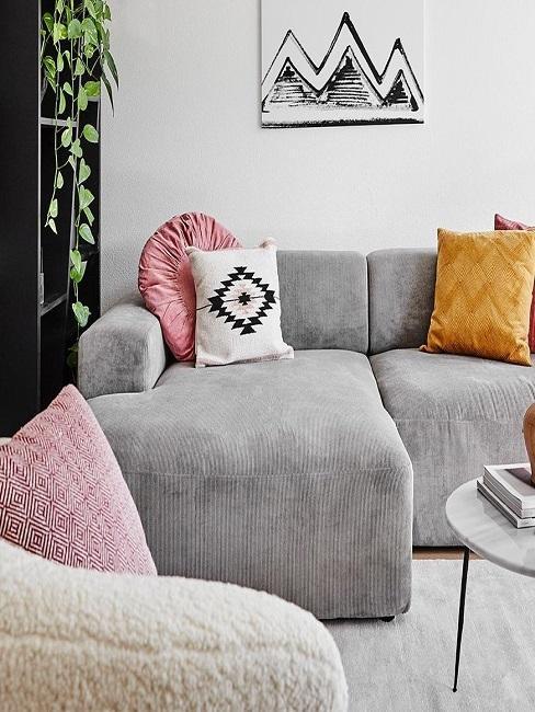 Hellgraue Cord Couch mit bunten Kissen
