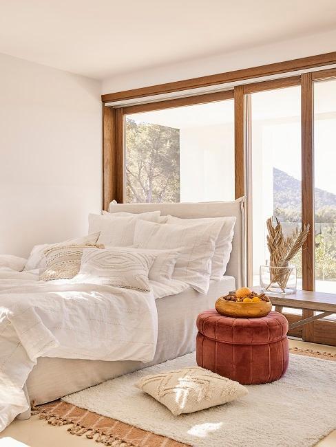 Modernes Schlafzimmer mit großer Fensterfront, Pouf und weißem Bett