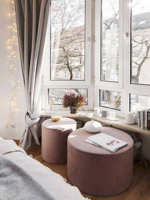 Zwei rosa Poufs am Fenster mit Deko