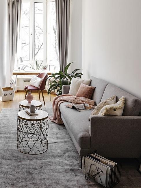 Wohnberiech in 1-Zimmer-Wohnung mit grauem Sofa, Teppich, goldenen Beistelltischen und Pflanze