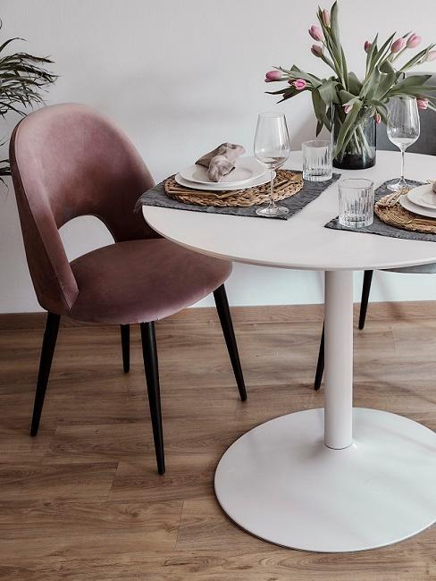 Runder, weißer Tisch und rosa Stuhl