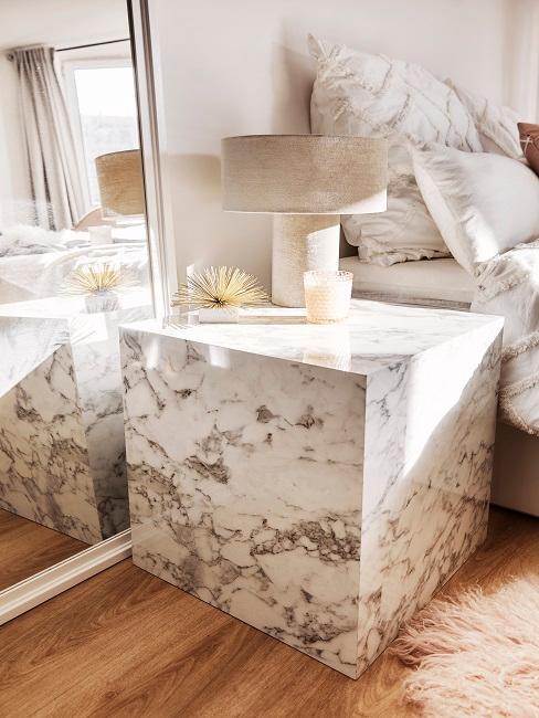 Nachttisch aus MArmor mit Tischleuchte und Deko neben Spiegel