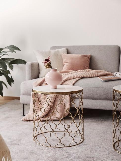Graues Sofa mit rosa Kissen und Plaid und goldenen Marmotischen