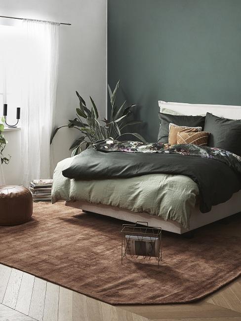 Grüne Wandfarbe im Schlafzimmer kombinieren mit braunem Teppich, grüner Bettwäsche und Pflanzen