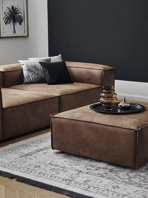 Wandfarbe Schwarz kombinieren mit braunem Ledersofa, grauem Vintage-Teppich und schwarz-weißen Kissen