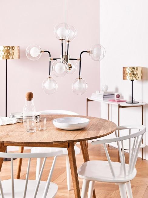 Pastellrosa Wand im Esszimmer mit Holztisch, weißen Stühlen und großer Pendelleuchte