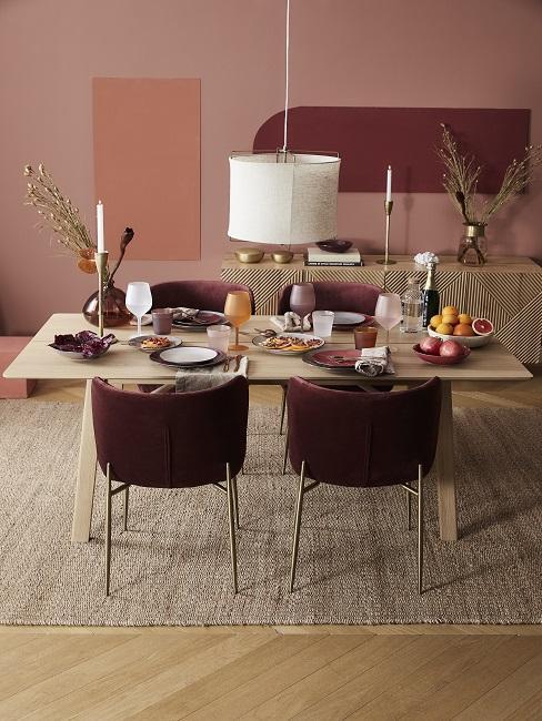 Wandfarbe Terracotta kombinieren im Esszimmer mit bordeauxroten Stühlen, Holztisch und Juteteppich