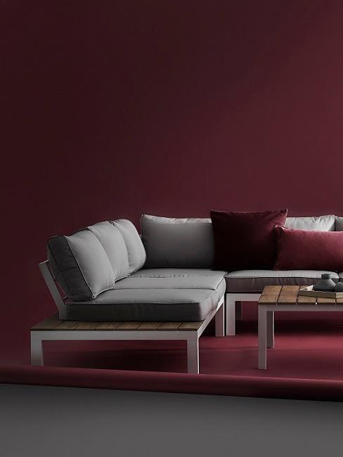 Wohnzimmer mit dunkelroter Wand, grauem Sofa und dunkelroten Kissen
