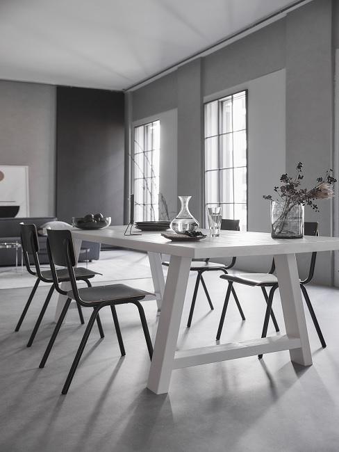 Grau-schwarze Wände in Zimmer mit weißem Esstisch und schwarzen Stühlen