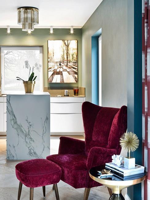 Wohnküche mit grüner Wand und Kücheninsel aus Marmor