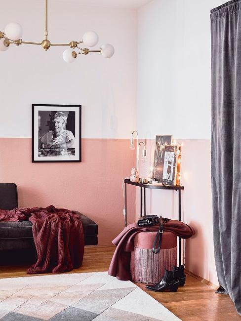 Zweifarbige Wände in Rosa und Weiß, Schwarz-Weiß-Bild an der Wand, Konsole mit Bildern und Pouf