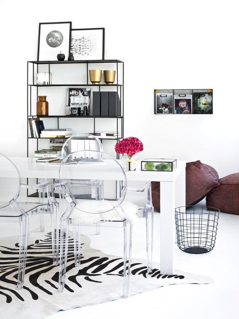 Estudio blanco decorado con estantería y mesa auxiliar negra y mesa y sillas transparentes